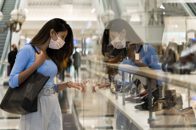 Donna che indossa maschera protettiva mentre guarda le calzature nel centro commerciale — Foto stock
