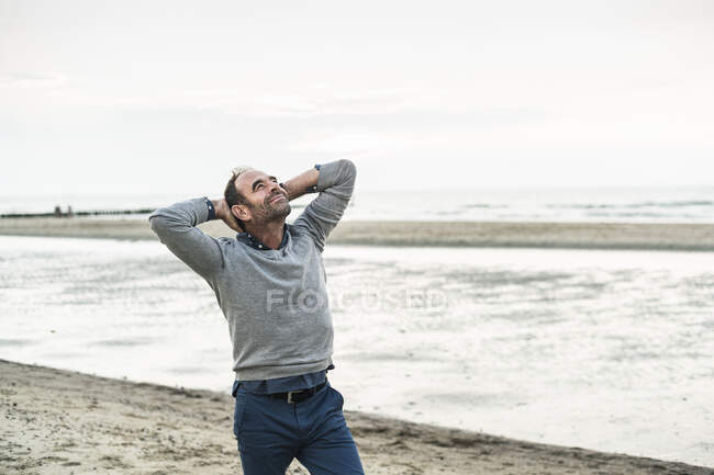 Carefree mature man with hands behind head standing against sea — Stock Photo