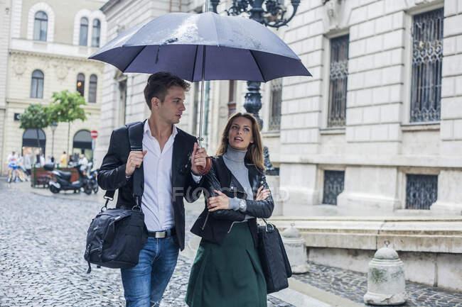 Зайнята жінка з колегою чоловічої статі гуляє під парасолькою на вулиці в місті. — стокове фото