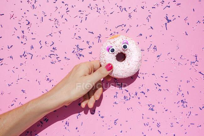 Рука женщины, держащей сладкий пончик с гуглистыми глазами — стоковое фото