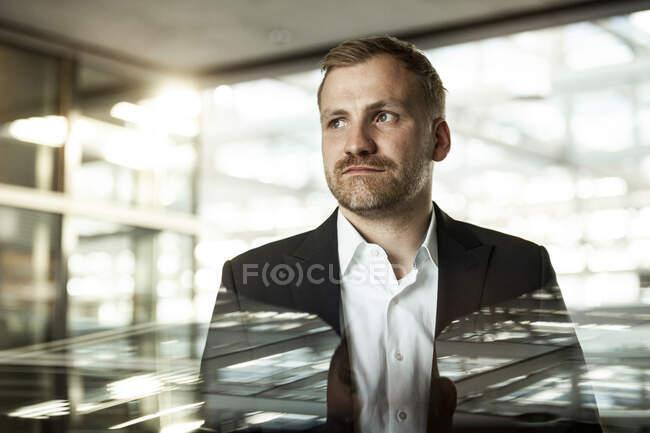 Portrait of businessman looking sideways in office building — Stock Photo
