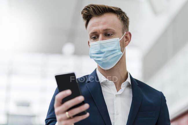 Бізнесмен користується мобільним телефоном і носить маску обличчя в місті. — стокове фото