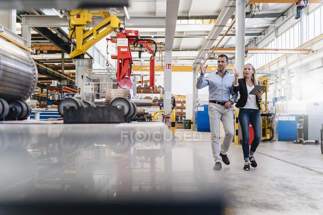 Бизнесмен и коллега указывают пальцем на фабрику — стоковое фото