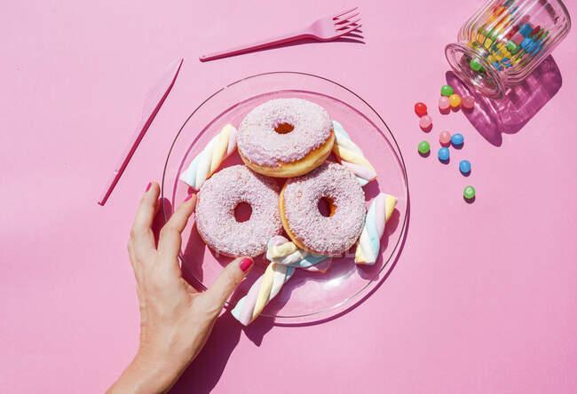 Mano de mujer recogiendo donut de plato de dulces - foto de stock