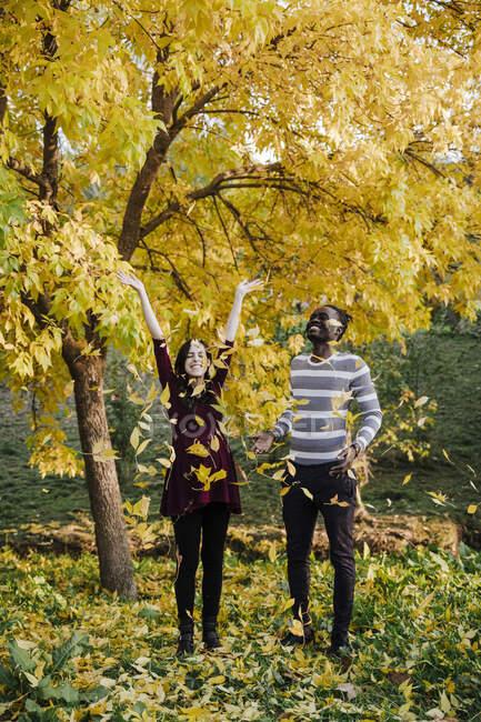Feliz pareja multi étnica jugando en el parque durante el otoño - foto de stock