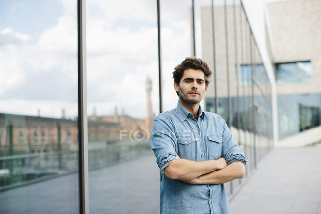 Handsome casual businessman with arms crossed standing against modern building — Stock Photo