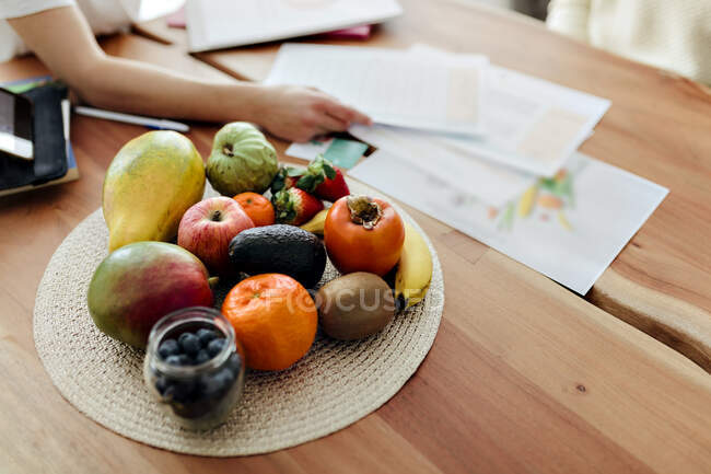 Mão de mulher organizando papéis por frutas mantidas na mesa em casa — Fotografia de Stock