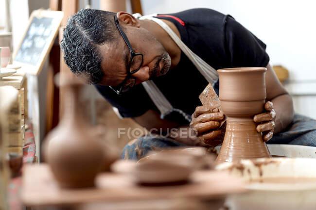 Чоловік, який займається виготовленням керамічних виробів на керамічному колесі в майстерні — стокове фото