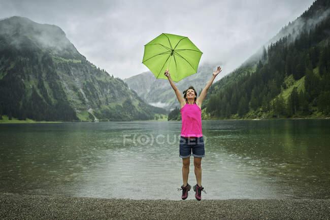 Mulher madura feliz segurando guarda-chuva enquanto saltava em Vilsalpsee lakeshore durante a estação chuvosa — Fotografia de Stock