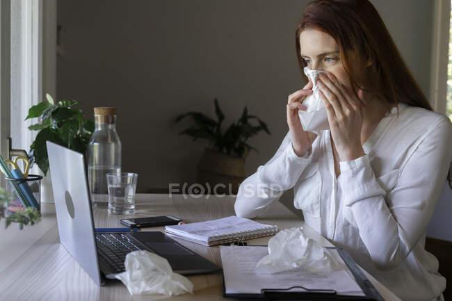 Mujer enferma hablando con el médico en el ordenador portátil en casa, la limpieza de la nariz con papel tisú - foto de stock