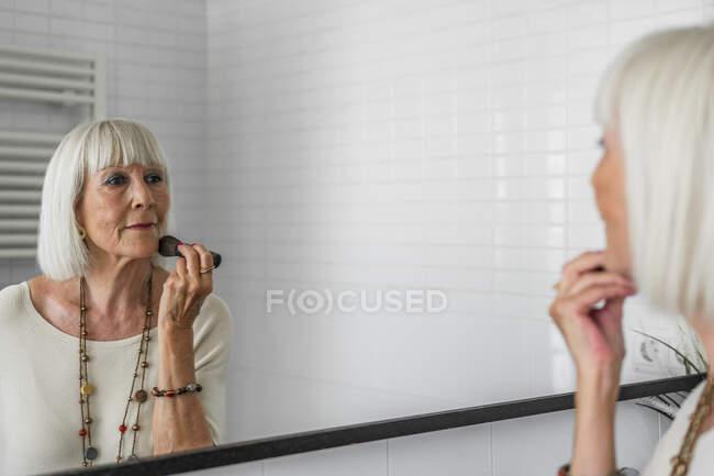 Mujer mayor que aplica maquillaje mientras se mira en el espejo en casa - foto de stock