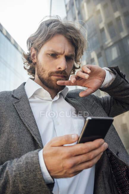 Обеспокоенный молодой предприниматель, использующий смартфон в финансовом районе города — стоковое фото