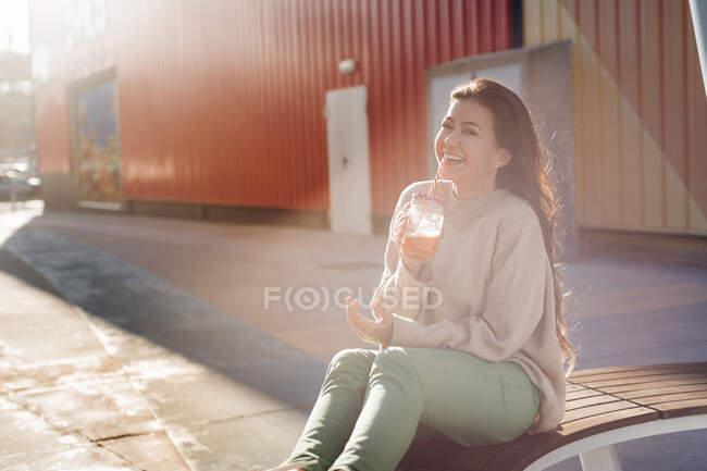 Joven alegre disfrutando de su bebida mientras está sentada en el banco contra el centro comercial - foto de stock