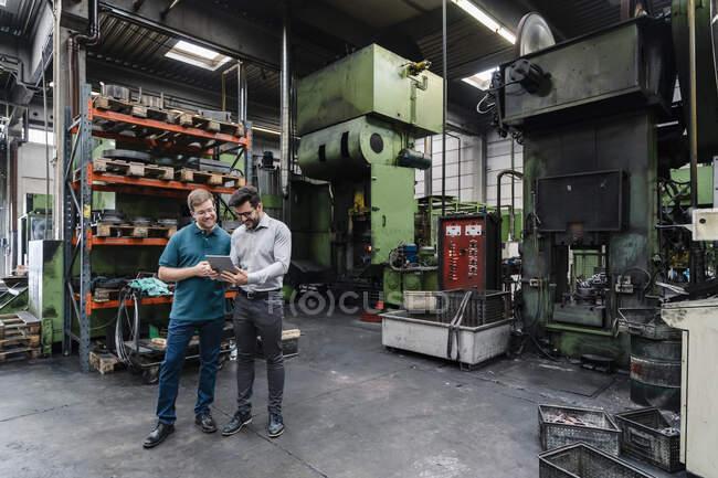Sorrindo colegas do sexo masculino usando tablet digital enquanto em pé fábrica de fabricação — Fotografia de Stock