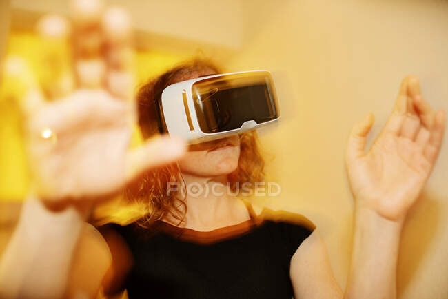 Close-up of mid adult woman looking through virtual reality simulator at home — Stock Photo