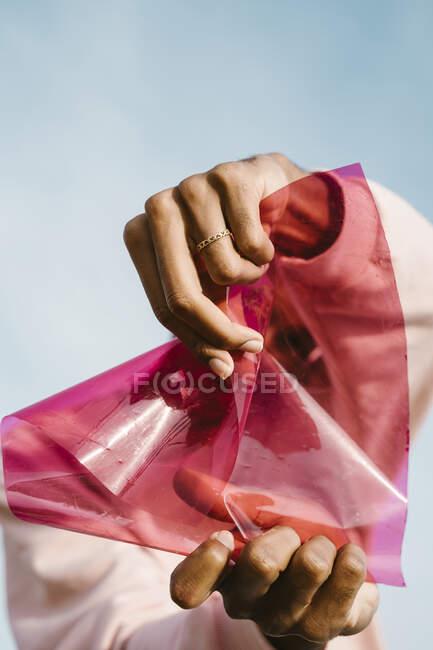 Hombre estrellándose plástico rosa contra el cielo - foto de stock