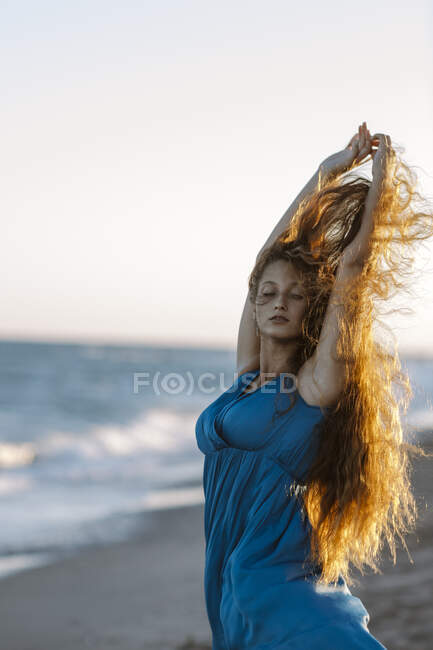 Young woman with hand raised dancing at beach during sunset — Stock Photo