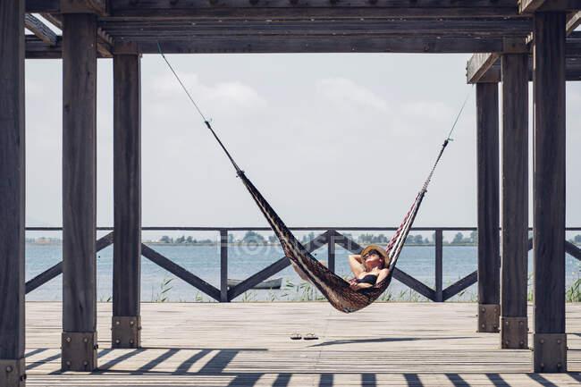 Розслаблена жінка лежить у гамаку, що звисає з металевої будівлі на набережній. — стокове фото