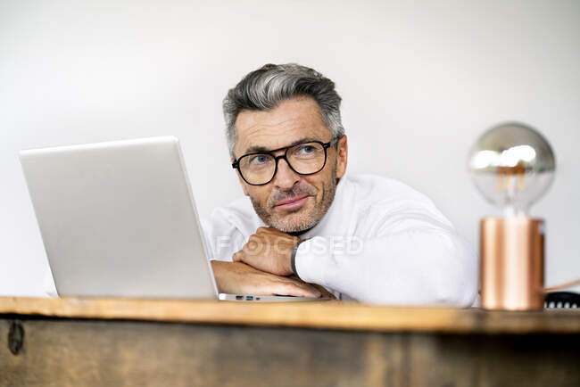 Großaufnahme eines männlichen Managers, der im Büro auf Laptop an Wand lehnt — Stockfoto