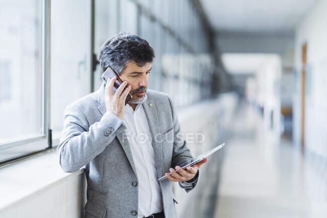 Чоловік професор розмовляє по мобільному телефону, дивлячись на цифрову табличку проти вікна в університетському коридорі — стокове фото