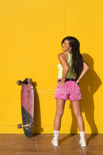 Young beautiful woman posing with longboard in front of yellow wall — стокове фото