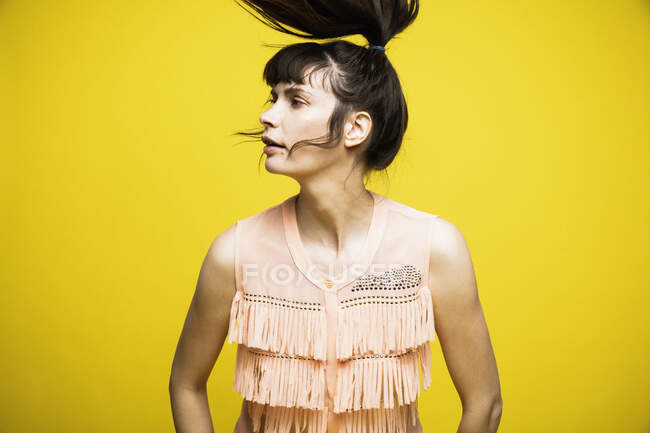Mulher jogando cabelo enquanto está em pé contra fundo amarelo — Fotografia de Stock