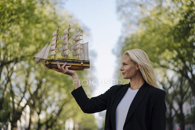 Rubia segura de mediana mujer de negocios adulta mirando modelo velero en la ciudad - foto de stock