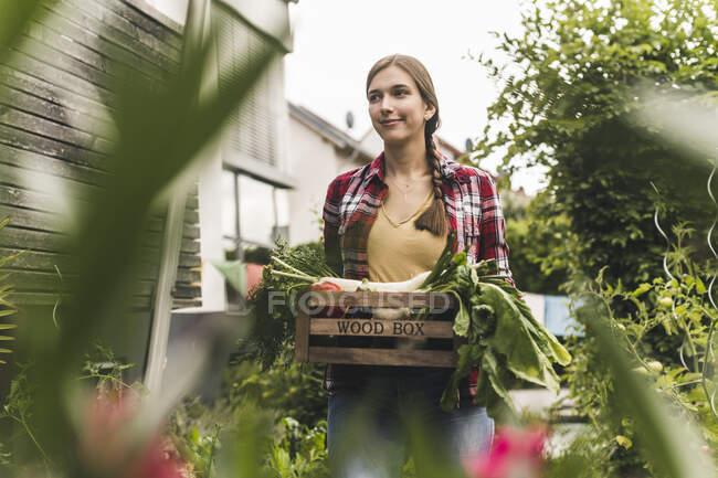 Молода жінка, що носить ящик, дивлячись убік, стоячи в городі овочів. — стокове фото