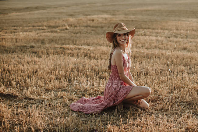 Mujer joven sonriente arrodillada en el campo de trigo al atardecer - foto de stock