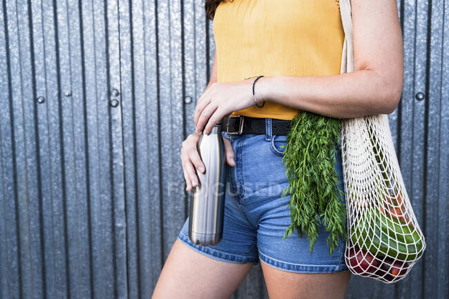 Woman holding bottle with reusable mesh bag while standing against metallic wall — Stock Photo