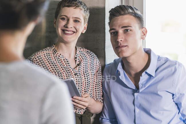 Колеги, які дивляться на бізнес-жінку, стоячи в офісі — стокове фото