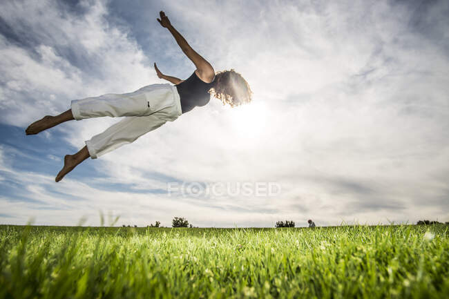 Young female athlete doing acrobatic activity in park against cloudy sky — стоковое фото