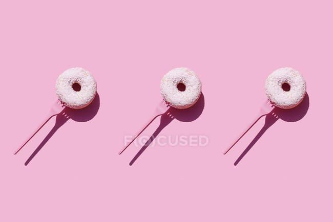 Estudio de horquillas con rosquillas dulces sobre fondo rosa - foto de stock