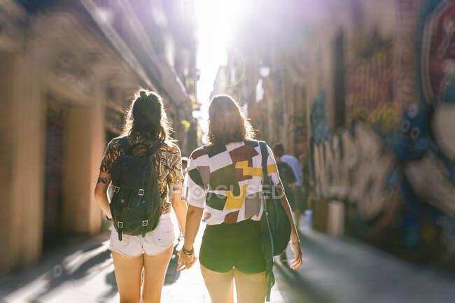 Лесбиянки прогуливаются по улицам города в солнечный день — стоковое фото