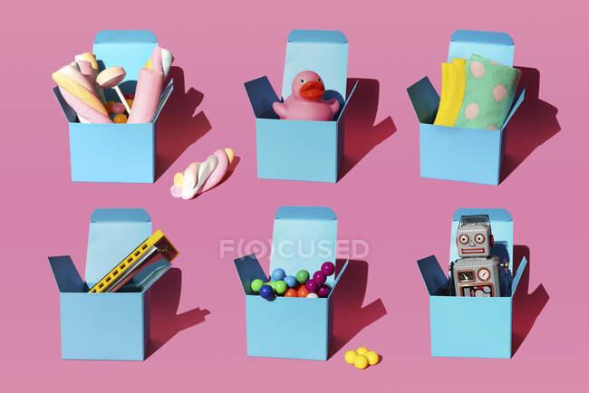 Патерн з коробками з різними подарунками, що складаються з губної гармоніки, пластикових сфер, старовинної іграшки робота, цукерок, качки каучуку і шкарпеток. — стокове фото