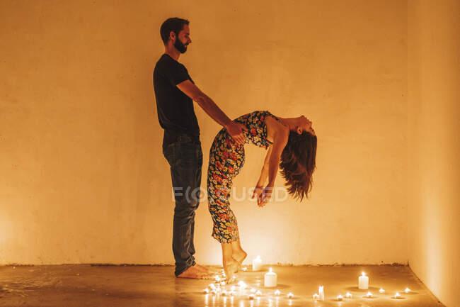 Hombre sosteniendo mujer doblando hacia atrás sobre velas encendidas en cuarto oscuro - foto de stock