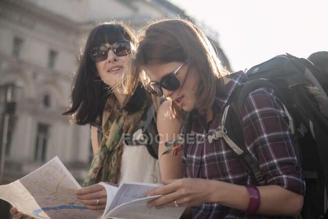 Donne in vacanza lettura mappa mentre seduti in piazza della città — Foto stock