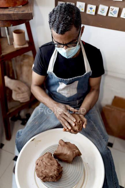 Чоловічий гончар у масці тримає глину, сидячи в майстерні. — стокове фото