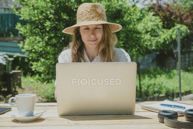Усмішка жінка працює сидячи і використовуючи ноутбук за столом на задньому дворі. — стокове фото