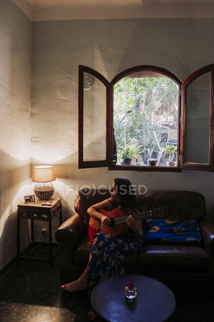 Young woman practicing guitar while sitting on sofa in living room — Stock Photo