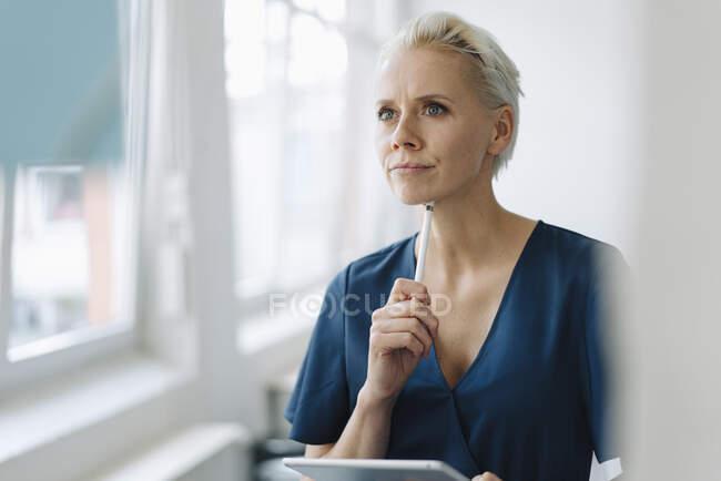 Думлива комерсантка тримає цифрову табличку і оцифровує ручку в офісі, яку видно через скло. — стокове фото