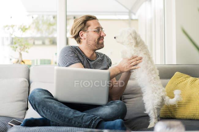 Hombre con portátil sosteniendo perro mientras está sentado en el sofá - foto de stock