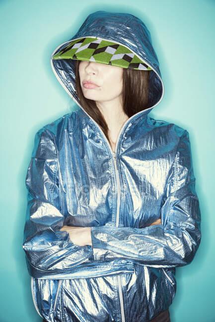 Зріла модель, одягнена в плащ і шапку, стоячи навпроти синього фону. — стокове фото