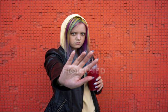 Портрет молодої жінки з пофарбованим волоссям, що піднімає руку перед червоною стіною. — стокове фото