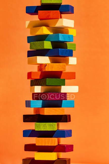 Colorful toy blocks stack against orange background — Stock Photo