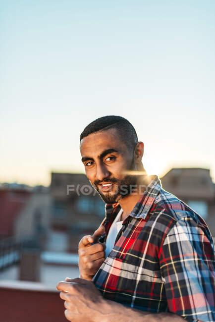 Uomo sorridente gesticolare mentre in piedi sul tetto della città — Foto stock