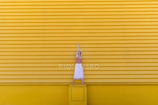 Ballerina with tiptoe dancing on seat against yellow wall — стокове фото