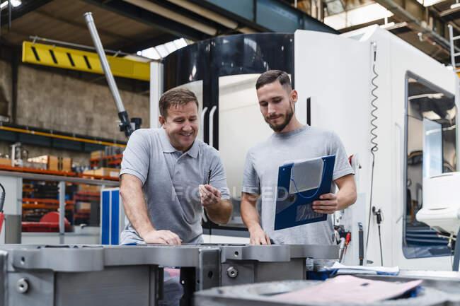 Maduro masculino técnico analisando produto de pé por jovem colega no industrial fábrica — Fotografia de Stock