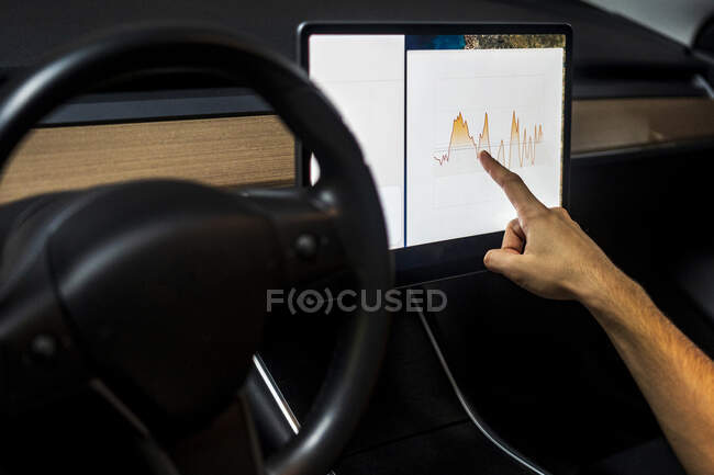 Male technician examining graph on digital tablet while programming in car — Stock Photo