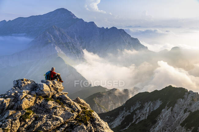 Hombre sentado y admirando el paisaje de montaña durante el amanecer en los Alpes bergamascos, Italia - foto de stock